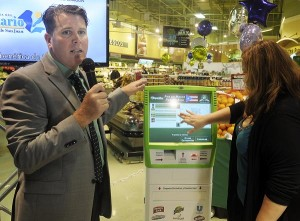 Blake Patterson, executive vice president for REMAG offers a demo of the kiosk to Cuponeando en PR Founder Edith Tapia. (Credit: © Mauricio Pascual)
