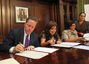 Secretary of State David Bernier signs off on the agreement between the government and Arcos Dorados to produce iceberg lettuce.